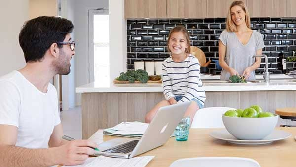 Happy family while mother working in kitchen, father on laptop and small happily sitting on table