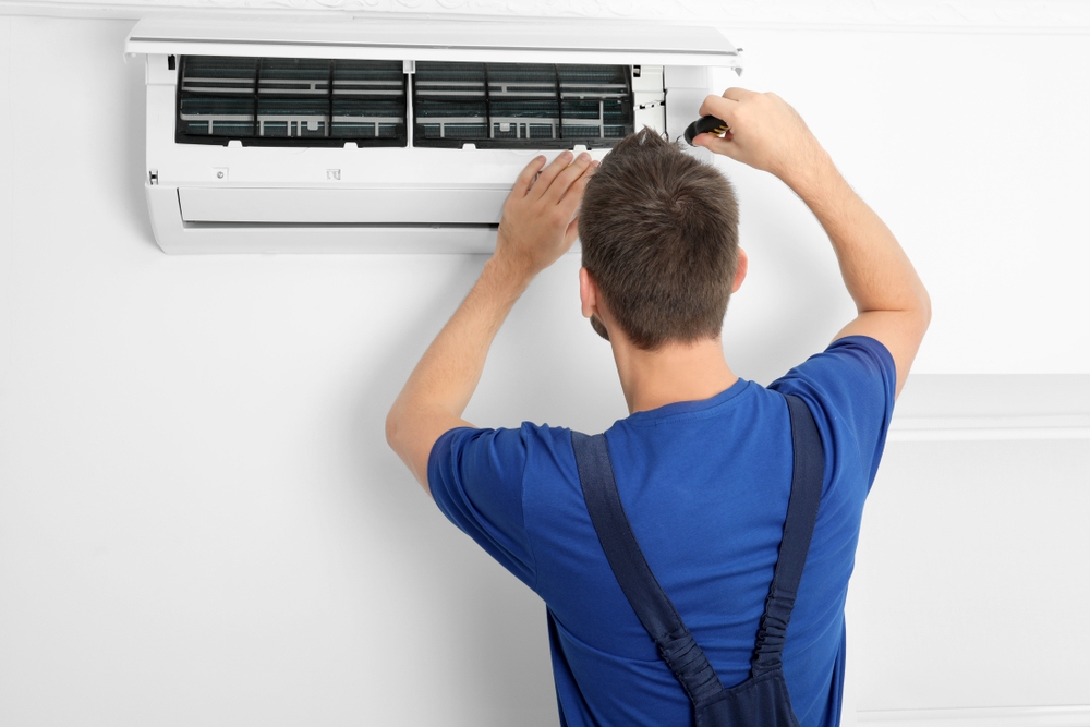 Male technician repairing air conditioner indoors.