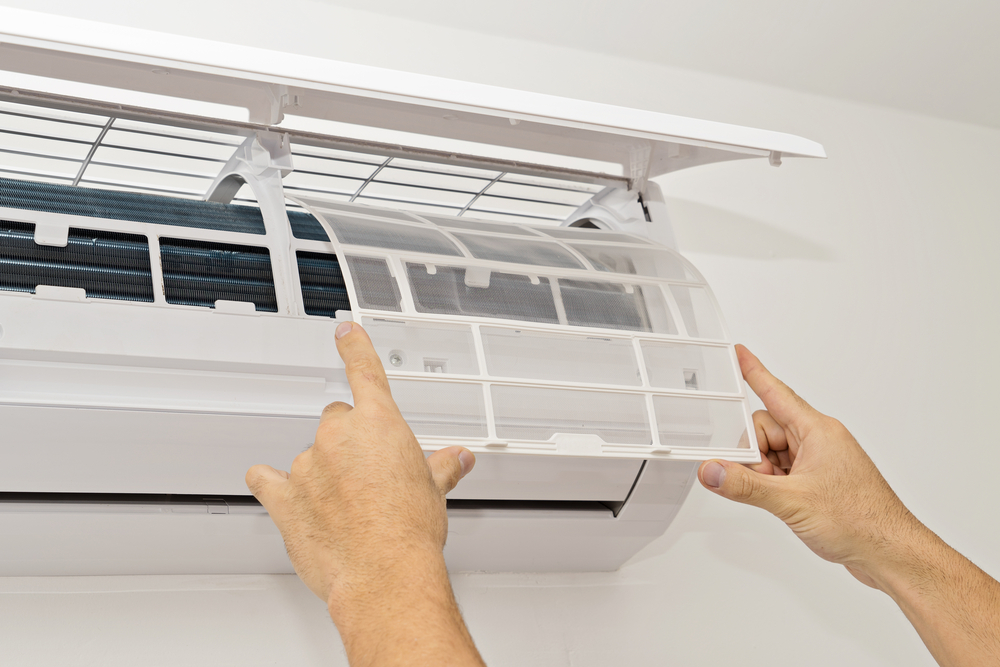Man changes the filter in the air conditioner.